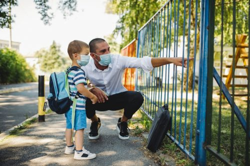 Business father and son going to kindergarten. They are wearing a medical face masks.